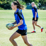 Three Luther College girls play touch rugby