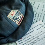 A closeup of Luther College archive documentation and a vintage flat cap