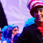 A Luther College student plays the Cat in the Hat, with other students performing in the background