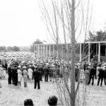 A crowd gathers in a historic black and white image of the bell tower